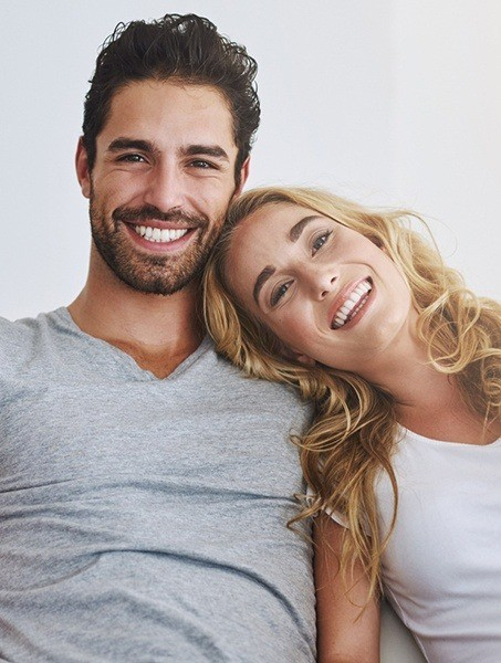 Smiling man and woman sitting together on couch