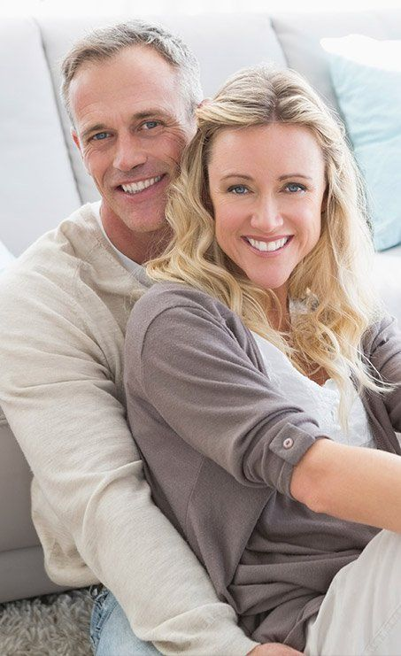 Smiling older man and woman on couch