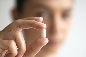 Hand holding white antibiotic tablet