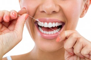 smiling woman flossing her teeth